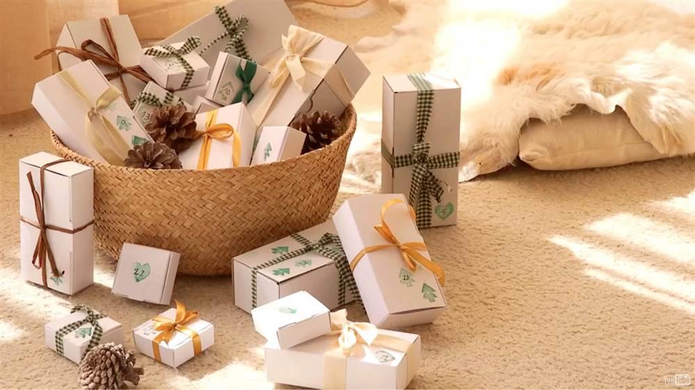 cesta-de-fibra-natural-con-cajas-de-regalo-con-lazos-y-pinas-sobre-alfombra-de-tonos-claros_1000x562_40730557